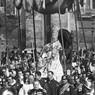 Seduto sulla sedia gestatoria, Pio XI benedice la folla radunata sulla piazza, accompagnato nella processione da militari e sacerdoti