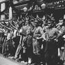 Folla radunata sul marciapiede di una strada berlinese fa il saluto nazista trattenuta da un cordone di uomini in uniforme del partito nazionalsocialista