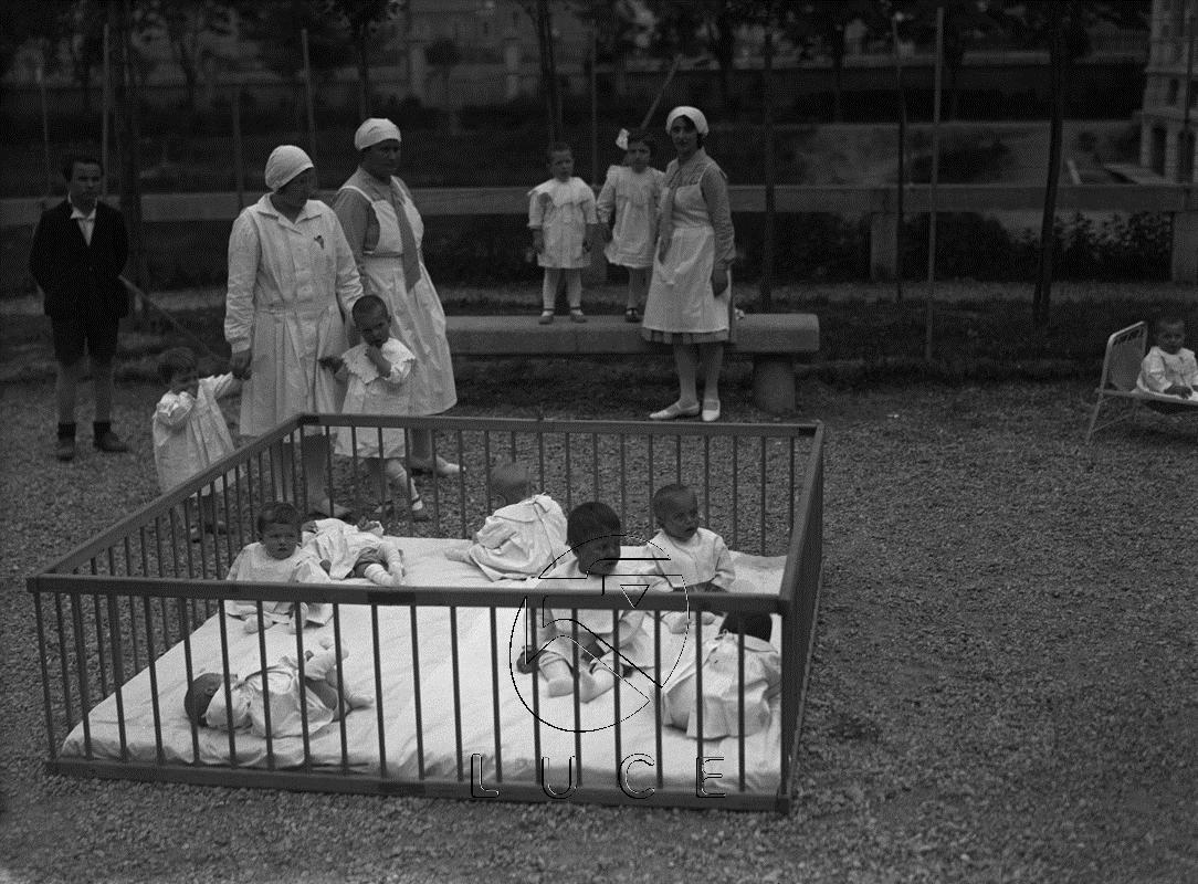 Archivio Fotografico Luce - Reparto Attualità, 21.05.1930 - Neonati e puericultrici di un istituto dell'O.N.M.I. di Milano in un giardino