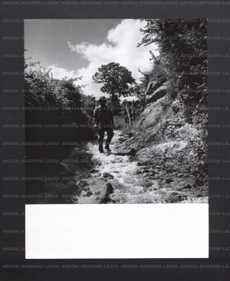Un uomo con cappello cammina sul letto di un torrente - La valigia sul letto torrent ...