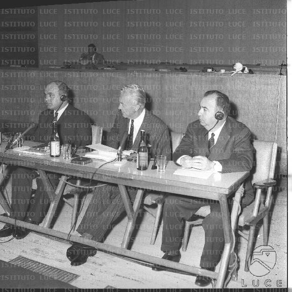 Carandini seduto al tavolo degli oratori tra due persone probabilmente straniere con le cuffie - Cuffie traduzione ...