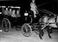 Hitler (che saluta) e Vittorio Emanuele III all'interno di una carrozza scoperta trainata da un cavallo; alle loro spalle due lacchè; ripresa in notturna