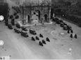 Inquadratura dall'alto del Colosseo verso l'Arco di Costantino durante il passaggio di colonne di autocarri