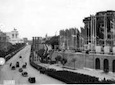 Inquadratura dall'alto del Colosseo verso Via dei Fori Imperiali durante il passaggio delle autorità in automobile