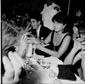 Anna Magnani fuma una sigaretta seduta ad un tavolo del Brigadoon, al suo fianco si scorge Franco Cristaldi